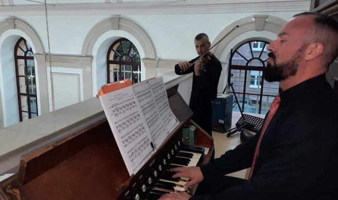 Čovjek s bradom u prvom planu svira na orguljama, a čovjek u pozadini svira na violini