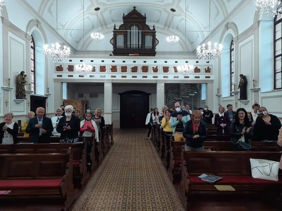 Grupa ljudi u prostoriji crkve aplaudira nakon završenog koncerta
